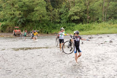 People with bicycles are crossing Rio Cano Negro in Costa Rica Stock Image