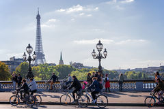 People on bicycles and pedestrians enjoying a car free day on Alexandre III bridge in Paris Stock Photos
