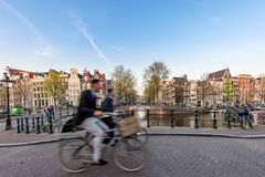 People bicycling through city streets on a beautiful sumer day i Stock Photos