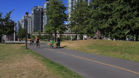 People bicycling urban landscape. Families bicycles Vancouver Canada summer stock footage