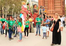 Masks and musicians supporting independence of Catalonia by Arc de Triomf in Barcelona. People in big tall masks of traditional Catalan figures and young Royalty Free Stock Photo