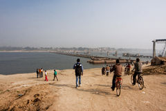 People on bikes and on foot heading towards the bridge over the Ganges Stock Photo