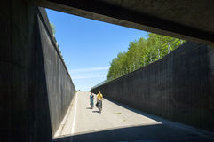People biking downwards into tunnel under highway Stock Image