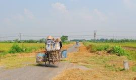 People biking on rural road in Vietnam Stock Images