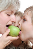 People biting apple. Group of people biting the same apple together stock photos