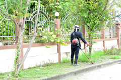 People black dress are mowers roadside close house. People are mowers roadside close house Stock Image