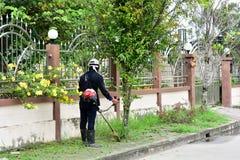 People black dress are mowers roadside close house. People are mowers roadside close house Royalty Free Stock Image