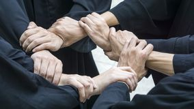People with black gowns join hand in circle loop. The people with black gowns join hand in circle loop Stock Image