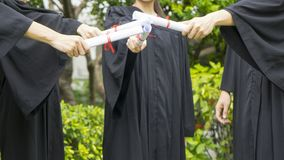 People with black graduation gowns hold diploma. The people with black graduation gowns hold diploma Royalty Free Stock Image