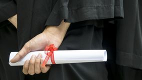 People with black graduation gowns hold diploma. The people with black graduation gowns hold diploma Stock Photography