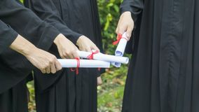 People with black graduation gowns hold diploma. The people with black graduation gowns hold diploma Royalty Free Stock Photos