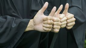 People with black graduation gowns thump up. The people with black graduation gowns thump up Stock Photography