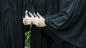 People with black graduation gowns thump up. The people with black graduation gowns thump up Royalty Free Stock Photo