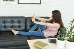 People, blogging and technology concept - young woman taking selfie on sofa stock image