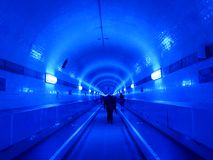 People in the blue illuminated Elbtunnel, in Hamburg, Germany Stock Images