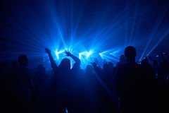People and blue lightshow. Silhouettes of people with raised hands against spotlights blue light show and musicians on the concert stage Stock Photo