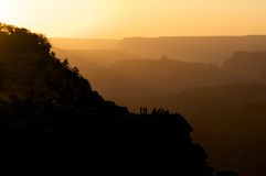 People on Bluff Amid Silhouetted Hills. Silhouette of people on a bluff in a dramatic desert landscape. Horizontal shot Stock Images
