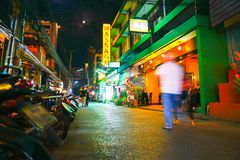 People blurred in motion walk down dark Asian city street toward Royalty Free Stock Photography