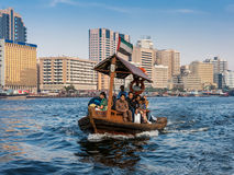 People on board of abra water taxi across the Creek in Dubai. People crossing the Creek from Deira to Bur by abra, a traditional wooden water taxi in Dubai Stock Image