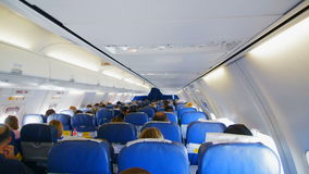 People are on board of the plane, people are sitting in blue armchairs, through the windows of the plane, the bright stock footage