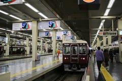 People board train at Osaka Hankyu Umeda Station Stock Image