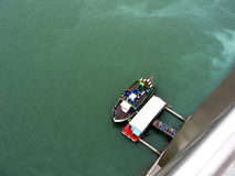 Tourists boarding a tour boat. Tourists boarding a boat for a tour. A view from above Royalty Free Stock Photos