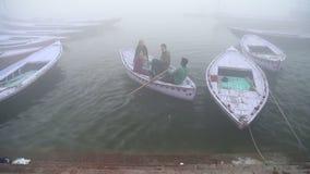 People in boat arriving at shore of Ganges river in Varanasi. VARANASI, INDIA - 25 FEBRUARY 2015: People in boat arriving at shore of Ganges river in Varanasi stock video