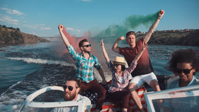 People on boat with colored smoke. Group of excited people sailing on boat playing with colored smoke bombs and celebrating Independence day Royalty Free Stock Photos
