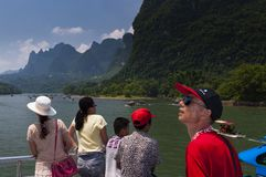 People in a boat cruising in the Li River and looking at the the tall limestone mountains near Yangshuo in China Royalty Free Stock Image