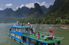 People in a boat cruising in the Li River and looking at the the tall limestone mountains near Yangshuo in China Royalty Free Stock Photography