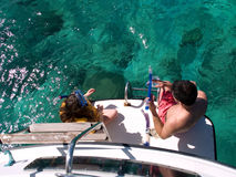 People on boat by ocean. Young girl with her father on a boat getting ready to snorkel at Buck Island, St. Croix, U.S. Virgin Islands surrounded by clear blue Stock Image