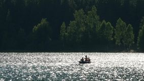 People in boat with paddles on mountain lake, summer relaxing day. UHD 4K stock video footage