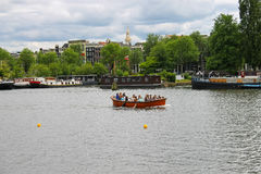 People in the boat on tours of the canals of Amsterdam Royalty Free Stock Photo