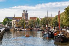People boating in small vessel in the Nieuwe Haven, the Grote Kerk royalty free stock images