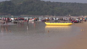 People and boats on Arabian sea beautiful resort beach in Goa, India. GOA, INDIA, JANUARY 11, 2014: people and boats on Arabian sea beautiful resort beach in Goa stock video footage