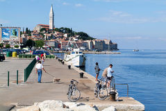 People on boats in front of Rovinj on Croatia Stock Photos