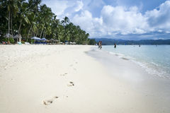 People on boracay island white beach philippines. Footprints in the sand leading towards people enjoying the clear shallow waters off beautiful boracay islands Royalty Free Stock Photography