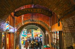 People at the Borough Market eating food purchased there as they walk through brick tunnel in London England UK 1 10 2018. People at the Borough Market eating Royalty Free Stock Images