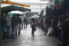 People at Borough market, hiding from the rain. Between the rows there is a girl with an umbrella Royalty Free Stock Photos