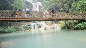 People on bridge looking viewpoint of Kuang Si Falls or Tat Kuang Si Waterfalls stock video footage