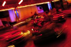 People on bumper car ride. People on bumper or dodgem cars ride at night with red light and slow motion blur effect Stock Photos