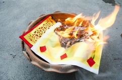People burn joss paper gold and silver paper for worship. With paper made to resemble money and burned as sacrificial offering for pray to god and memorial to Royalty Free Stock Photo