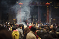 People burning incense in temple Stock Images