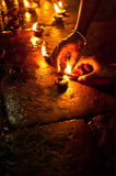 People burning oil lamps as religious ritual in Hindu temple Royalty Free Stock Photo
