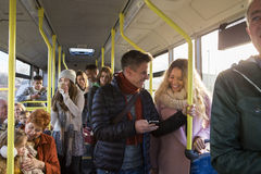 People on the bus. Different people can be seen travelling on the bus. Some are talking to other people, others are using technology or looking out the window Royalty Free Stock Photo