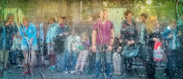 People at the bus stop during the rain. Are waiting for a bus stock images