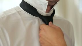 Close-up of man helping man and adjusting tie on his neck at home. stock video