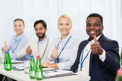 People at business conference showing thumbs up. Business, gesture and education concept - group of happy people at international conference showing thumbs up Stock Photography
