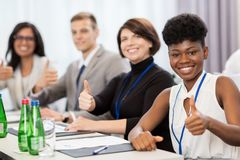 People at business conference showing thumbs up. Business, gesture and education concept - group of happy people at international conference showing thumbs up Royalty Free Stock Image