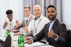 People at business conference showing thumbs up. Business, gesture and education concept - group of happy people at international conference showing thumbs up Royalty Free Stock Photos